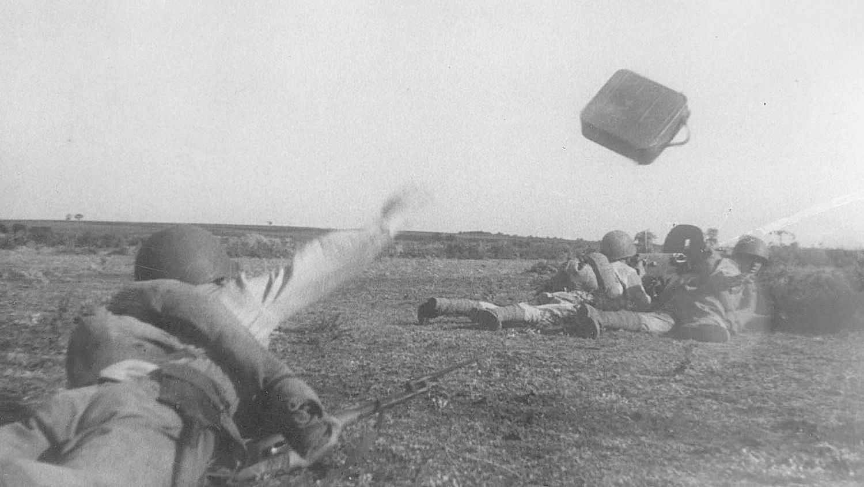 Подносчик боеприпасов гвардии младший сержант С. Кузьбанов бросает коробку с пулеметными лентами расчету станкового пулемета «Максим». 1944 (Фото — Ольга Ландер)
