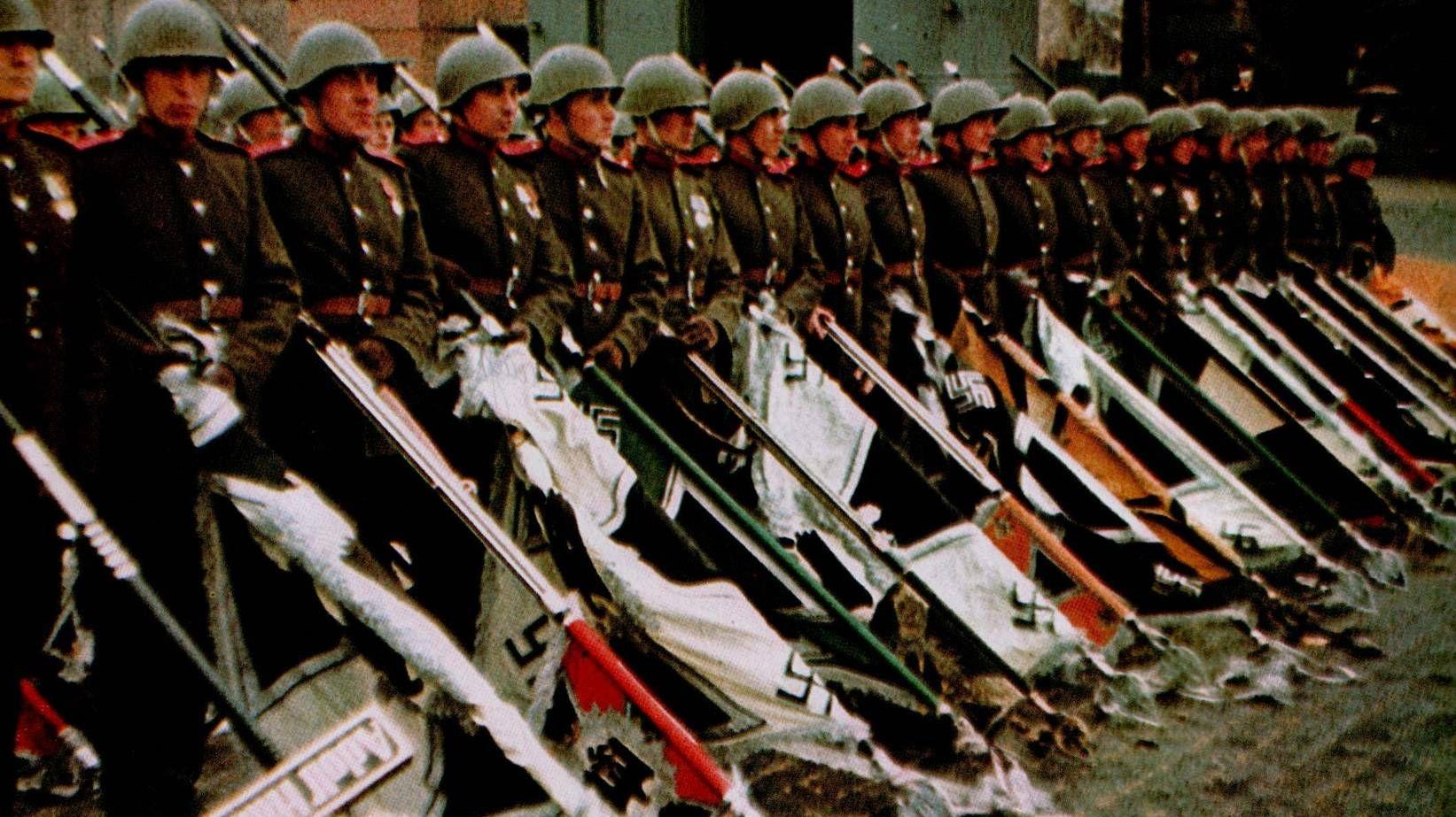 Советские солдаты бросают фашисткие знамена на землю преред Мавзолеем. Москва. 1945