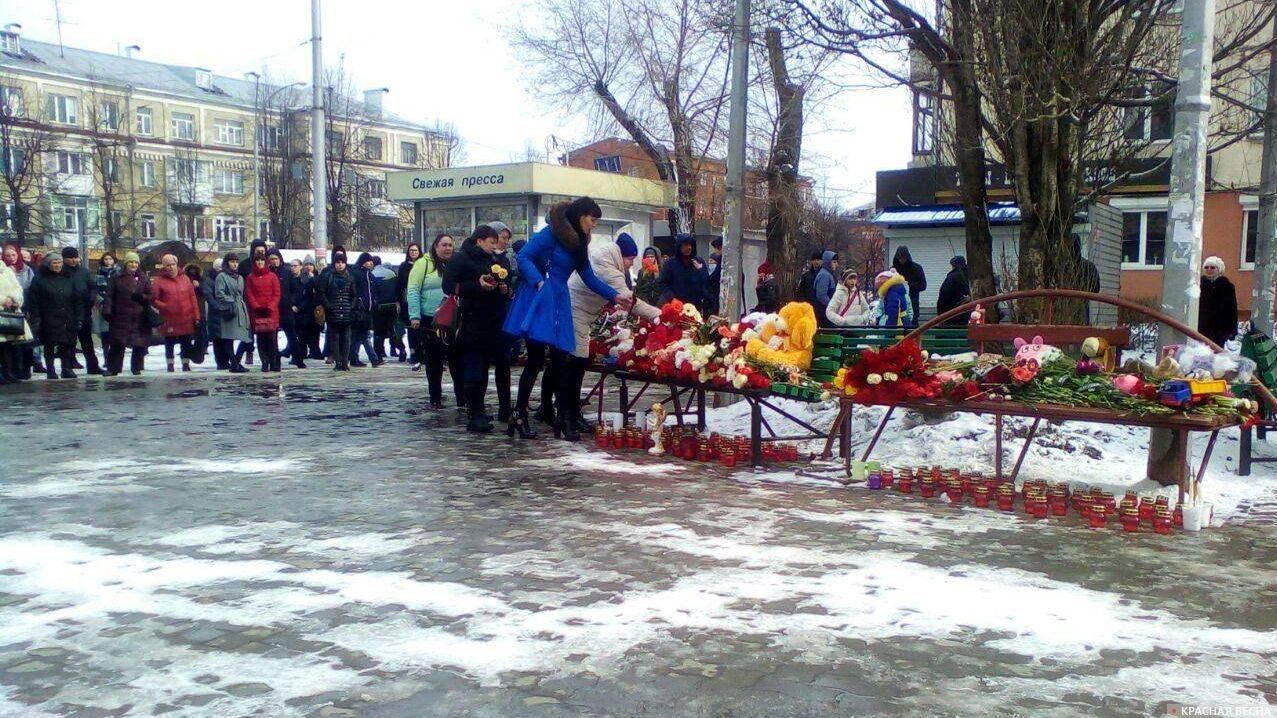 Цветы, детские игрушки и свечи в память о погибших