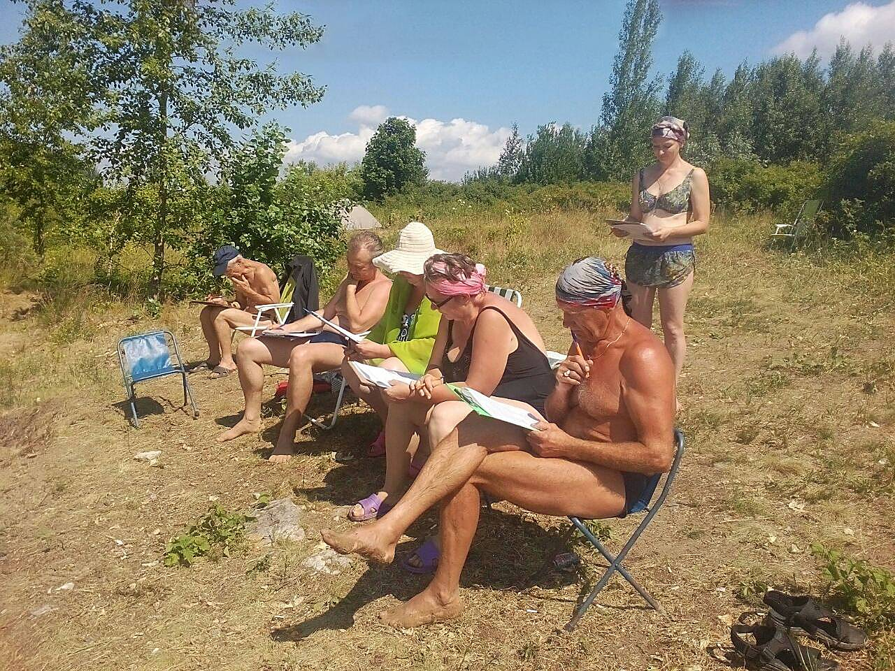 Отдыхающие на пляже с анкетами АКСИО
