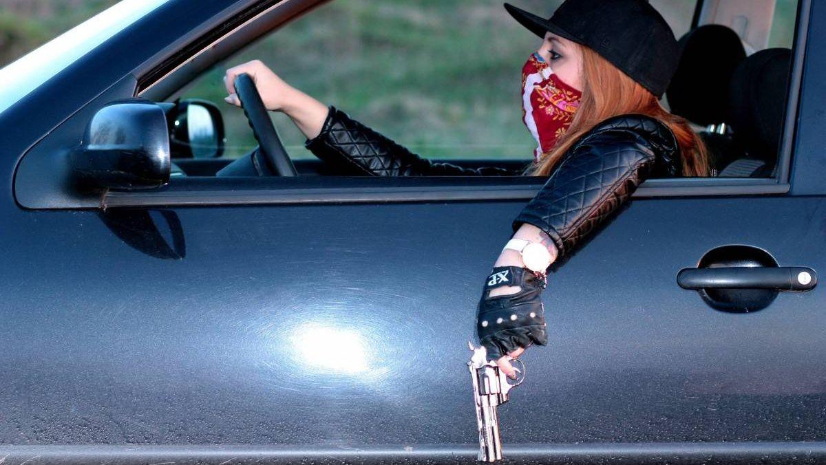 Девушка в автомобиле с пистолетом