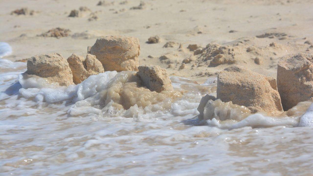 Море смывает замок из песка