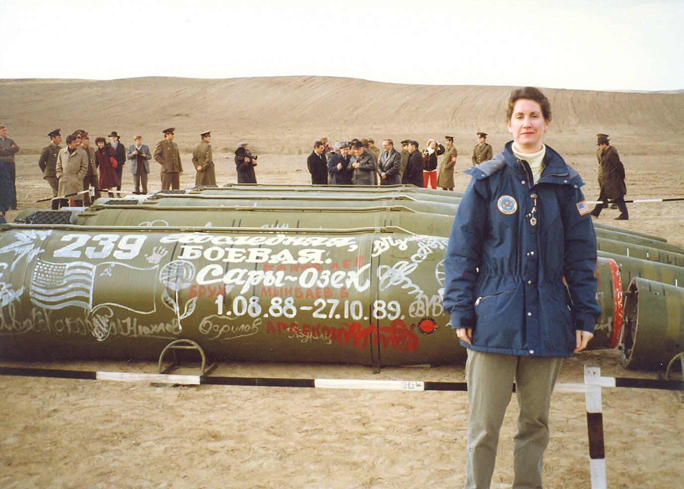Эйлин Маллой — руководитель группы контроля за вооружениями при посольстве США в Москве на фоне ракет подлежащих утилизации на базе Сары-Озек. 11 мая 1990
