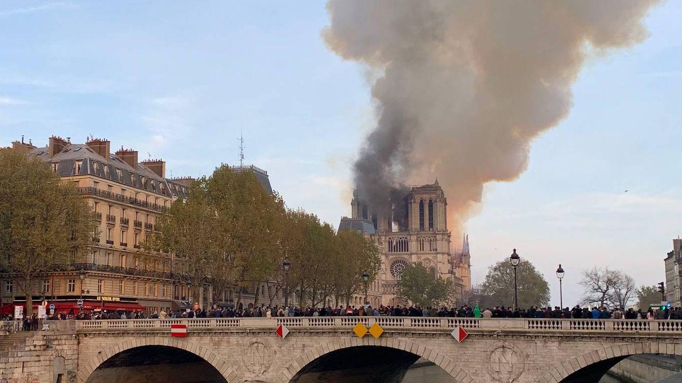 Люди наблюдают пожар в Нотр-Дам-де-Пари