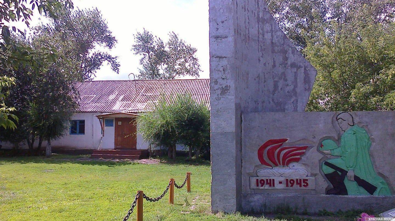 Лопарёвская школа на фоне памятника погибшим в Великой Отечественной войне