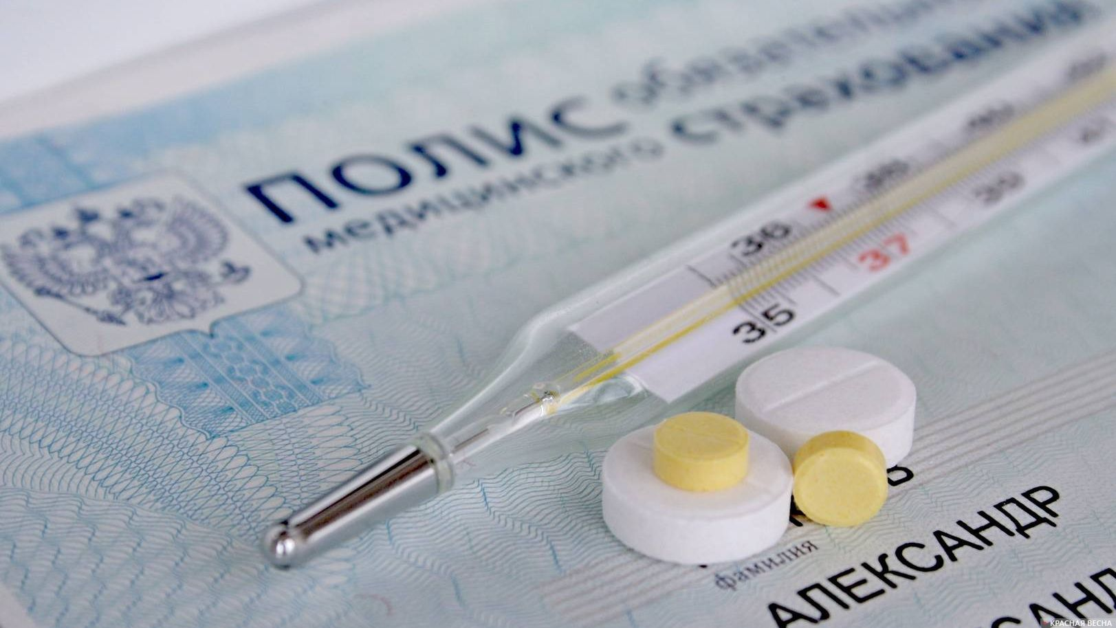 Термометр и таблетки на медицинсокм полисе