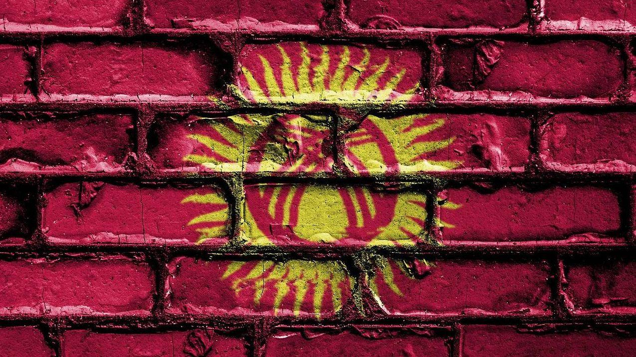 Флаг Киргизии на фоне кирпичной стены