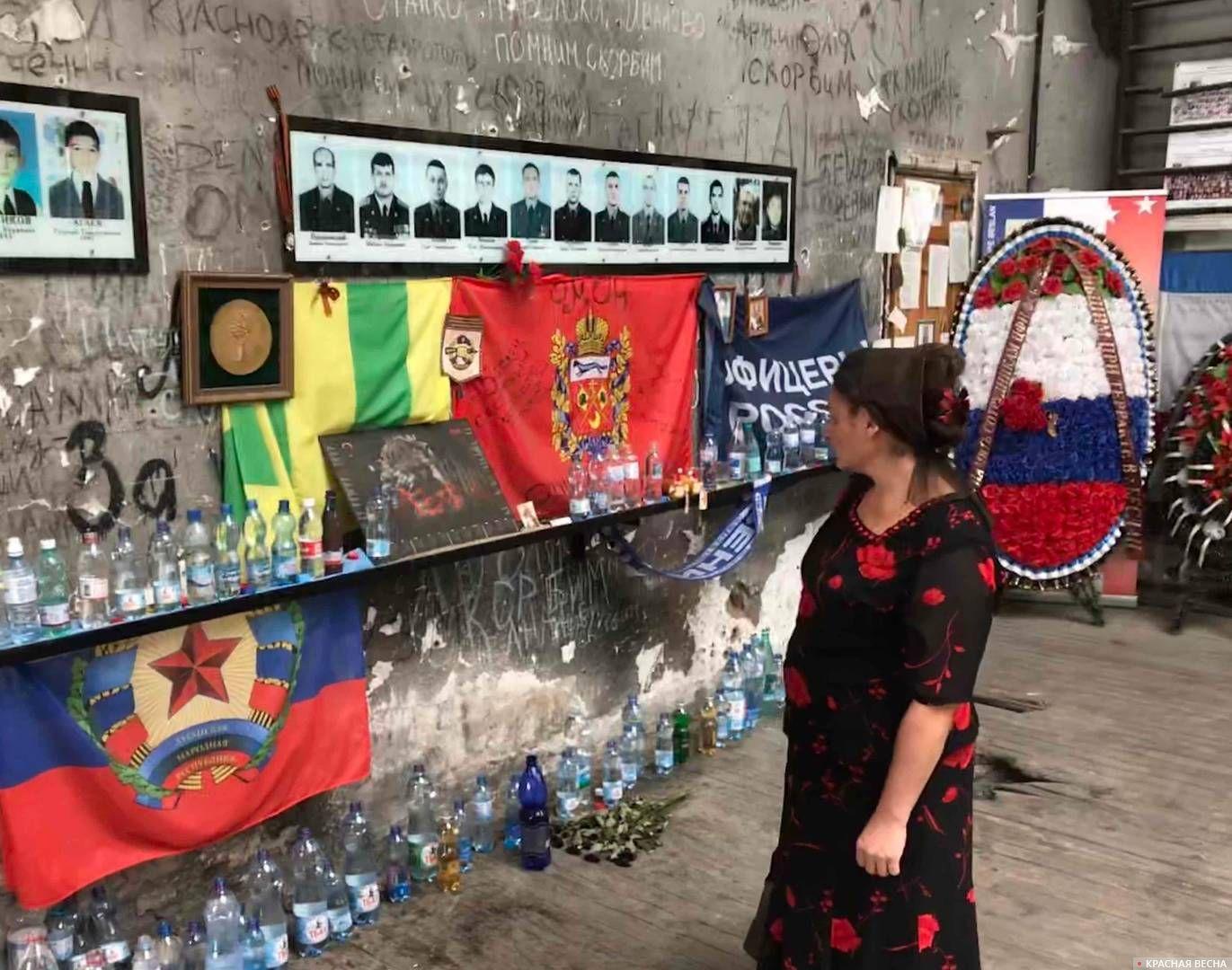 Женщина осматривает символику, принесенную в спортивный зал школы №1 Беслана