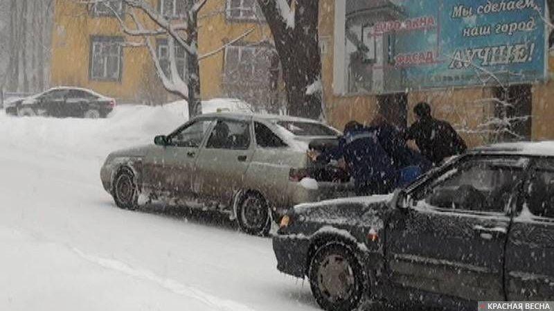 Люди помогают подняться автомобилю в гору