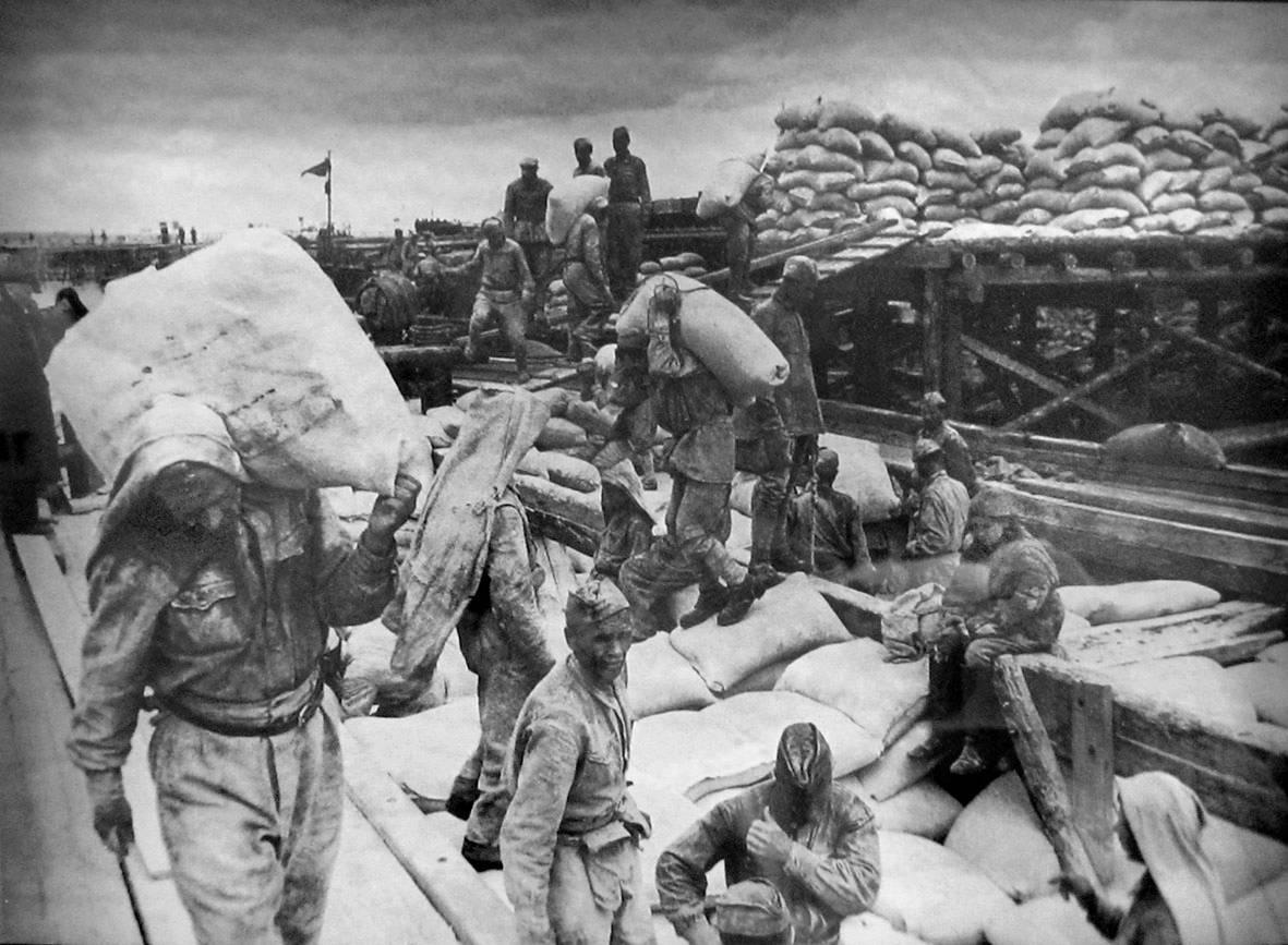Фотография из филиала ЦВММ «Дорога жизни». Советские солдаты разгружают баржу с мукой  в порту Осиновец