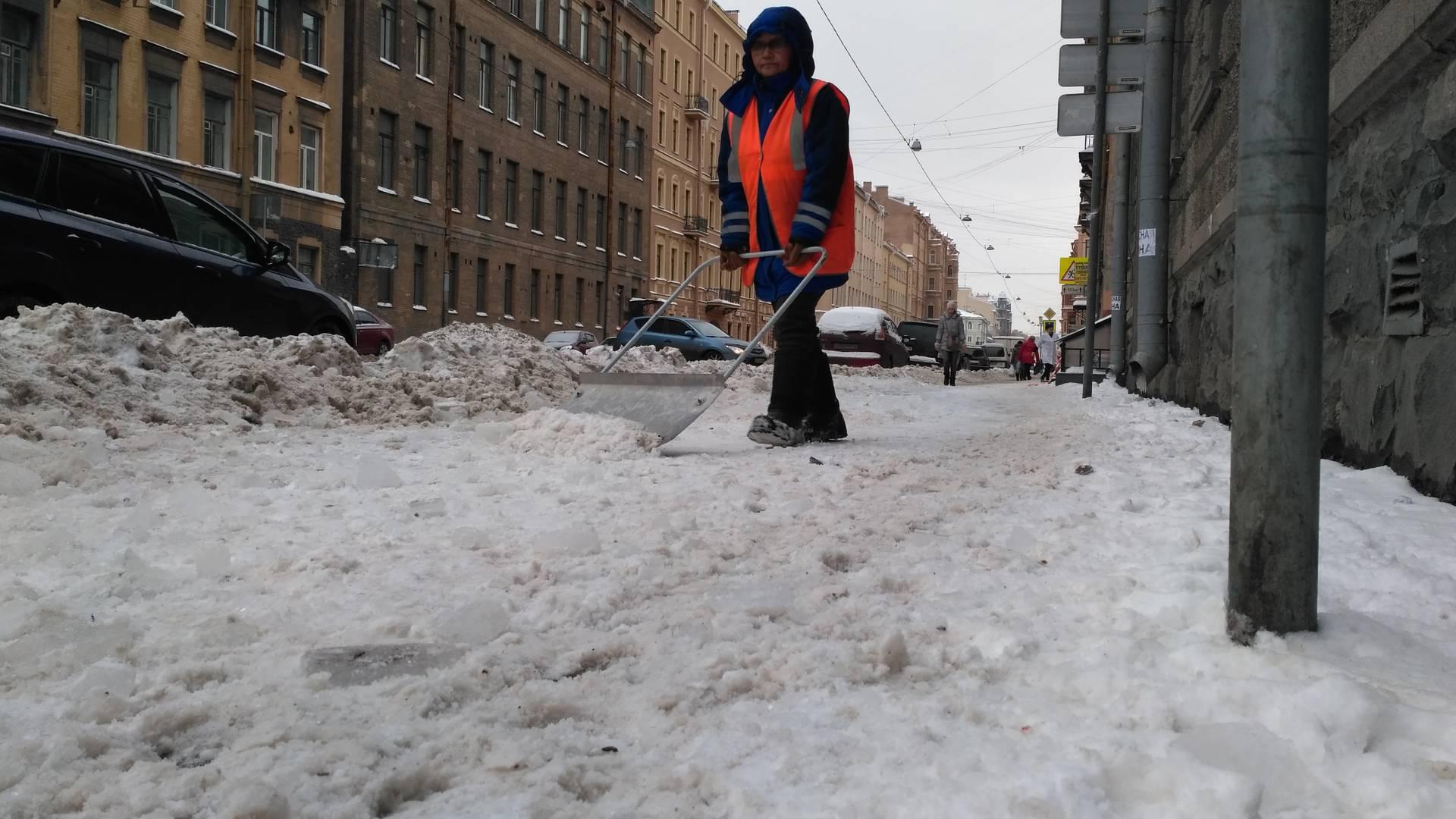 Снег и лед сброшены с крыши на тротуар, теперь их убирают на проезжую часть. Санкт-Петербург