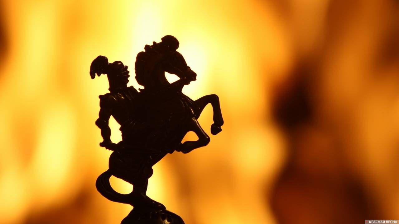 Фигурка воина на коне на фоне огня