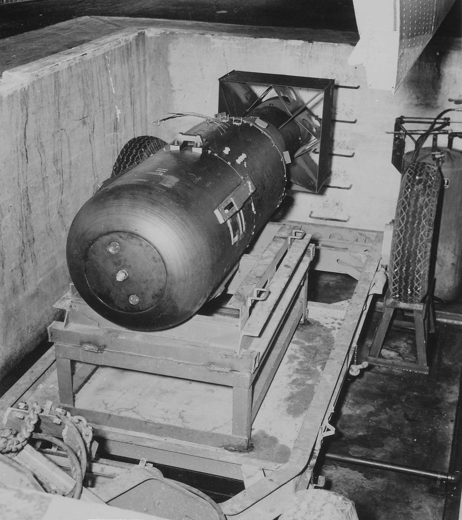 Атомная бомба «Малыш» покоится в яме под шлюзом бомбардировщика B-29 Superfortress «Enola Gay» на базе 509-ой сводной группы на Марианских островах в 1945 году. «Малыш» составлял 3 м в длину и весил 4 000 кг, и содержал всего 64 кг урана, который использовался для запуска цепочки атомных реакций и последующего взрыва.