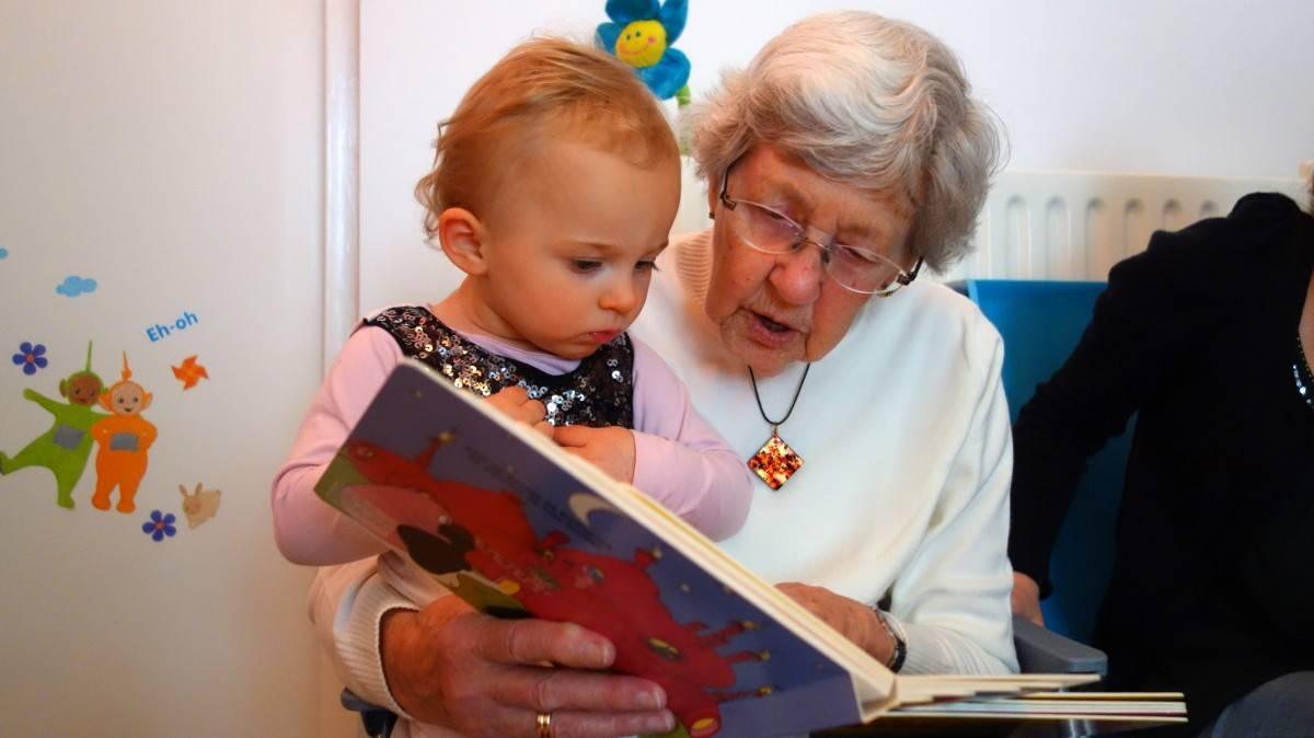 бабушка читает ребёнку книжку