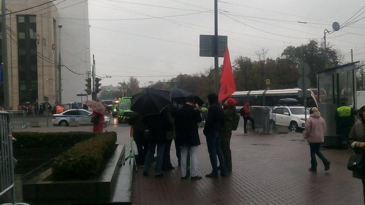 Люди под красным флагом на митинге либеральной оппозиции