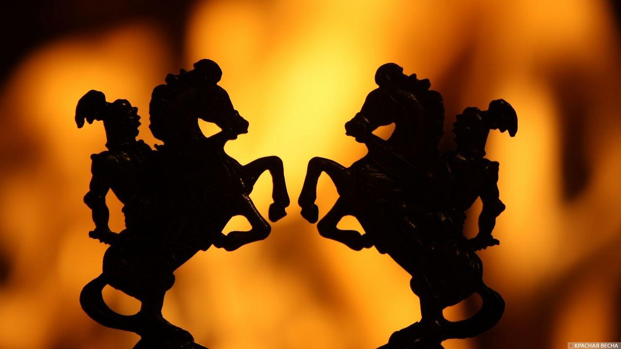 Фигурки воинов на коне на фоне огня