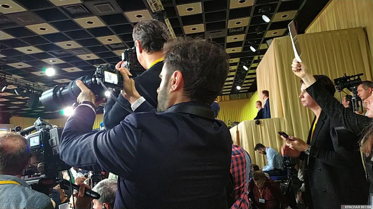 Журналисты на задних рядах тоже пытаются задать вопрос