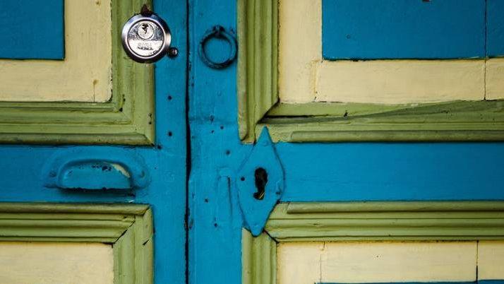 Старая жёлто-блакитная дверь с новым замком