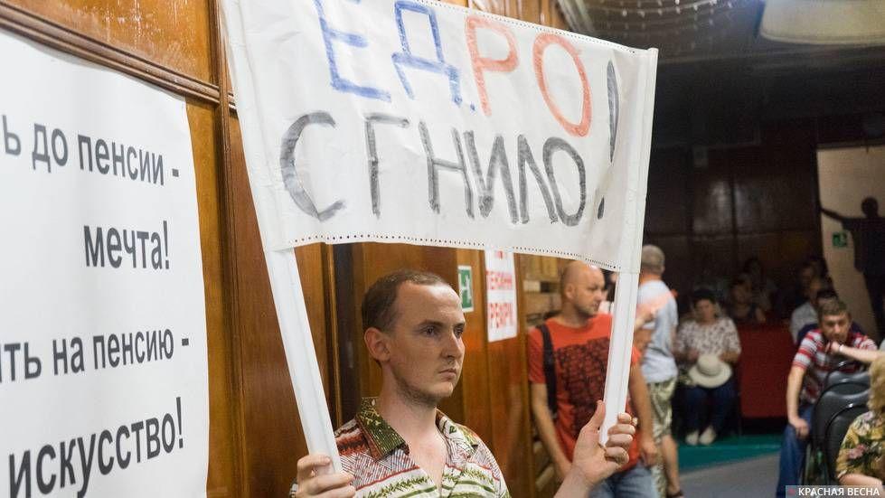Активист держит плакат «ЕДРО Сгнило!» на собрании КПРФ против пенсионной реформы