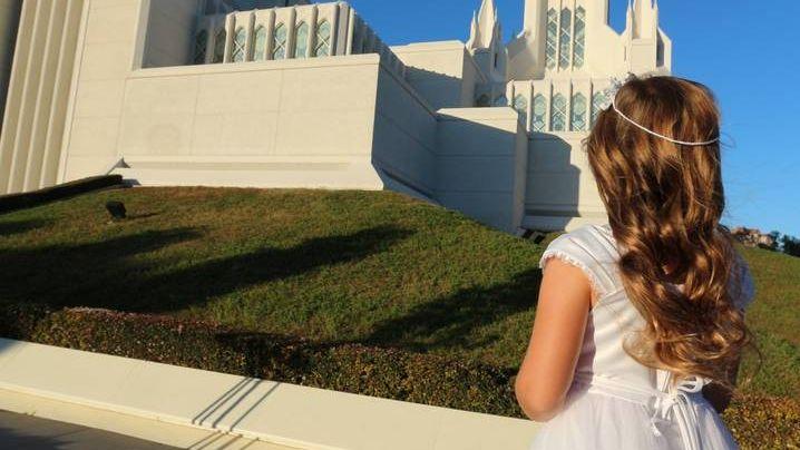 Девушка в свадебном наряде перед входом в церковь мормонов